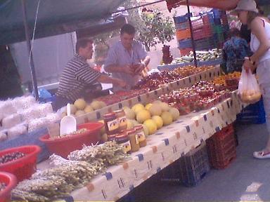 朝市にて、果物から瓶詰めまでいろいろ売る農家の人