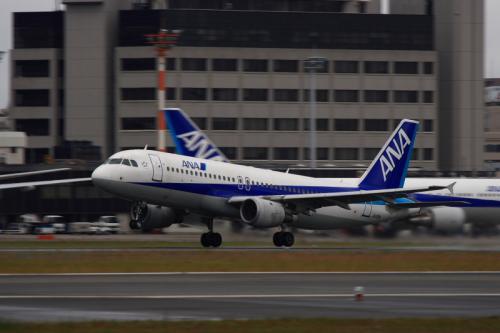 ANA A320 NH521@RWY14Rエンド脇再開発地区(by EF100-400)