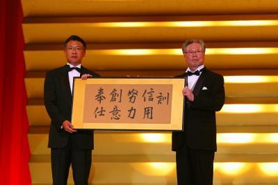 写真キャプション=社訓の額が鈴木社長から韓裕新社長に手渡される