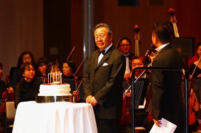 写真キャプション=記念コンサートでお祝いのケーキを贈られた韓会長